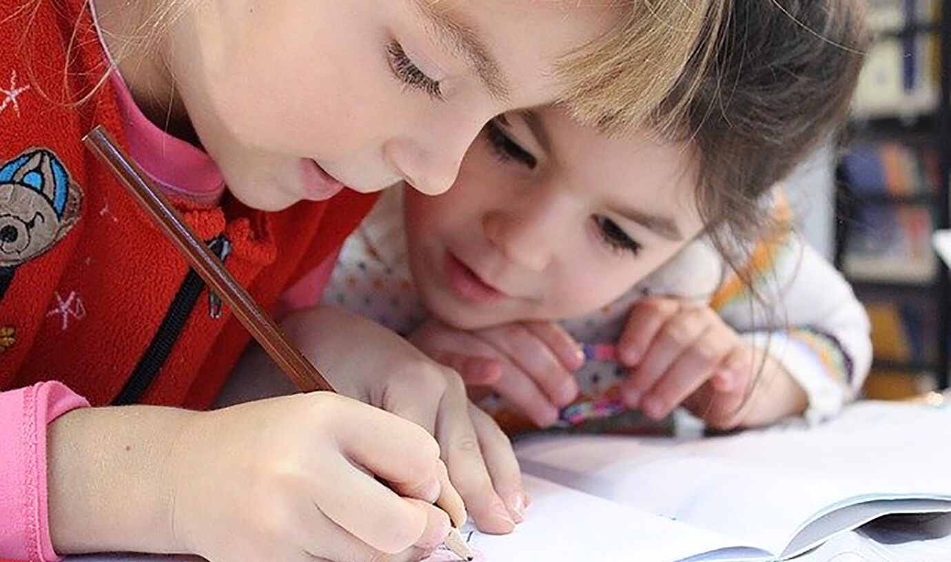 Two boys writing in a notebook